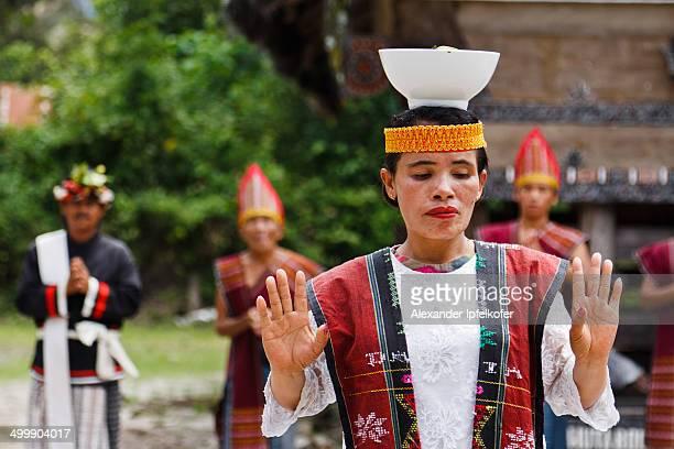 Female Batak dancer balancing a rice bowl on her head during the Traditional Batak dance performance at the Huta Bolon Village , Simanindo, Samosir...