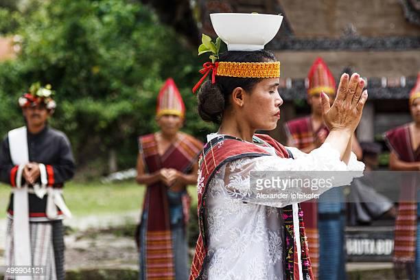 Female Batak dancer balancing a rice bowl on her head during the Traditional Batak dance performance at the Huta Bolon Village .