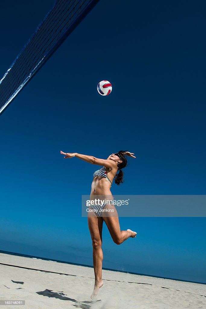 Female beach volleyball player hitting ball : Stock Photo