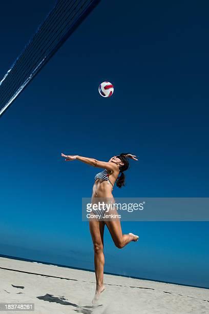 Female beach volleyball player hitting ball