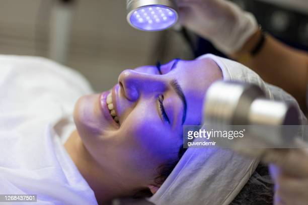 female beautician doing blue light therapy on face of pretty young woman - beauty treatment stock pictures, royalty-free photos & images