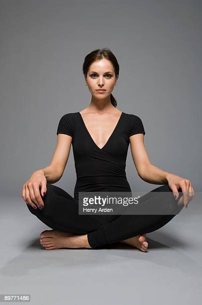 female beauty in catsuit yoga position - cross legged stock pictures, royalty-free photos & images
