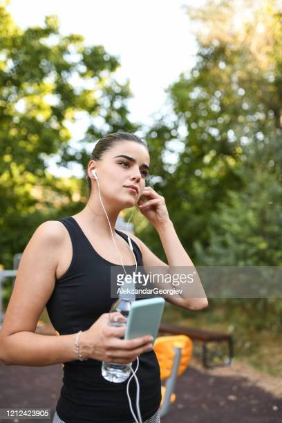 female beauty listening to music while working out in park - colors soundtrack stock pictures, royalty-free photos & images