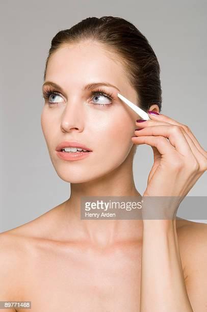 female beauty plucking eyebrow