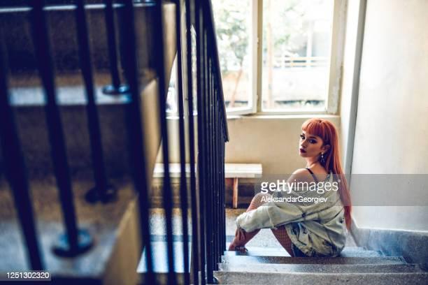 weibliche schönheit sitzt auf wohnung treppe - verführerische frau stock-fotos und bilder