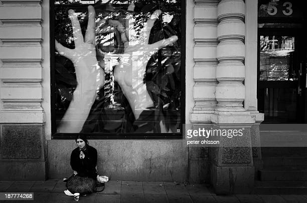 Female beggar in front of a store window with a huge poster of a woman shouting.
