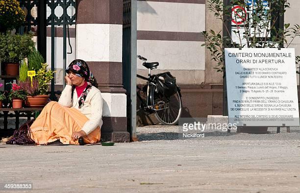 Fêmea Mendigo sentado fora um Cemitério