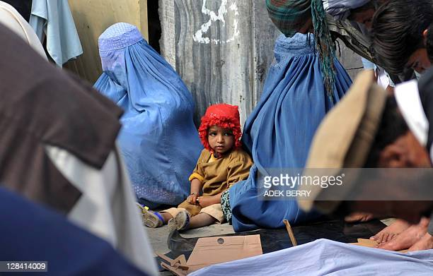 Female beggars and a young girl sit as Afghan worshippers hold weekly Friday prayers in Kabul on October 7 2011 Afghans have marked 10 years since US...