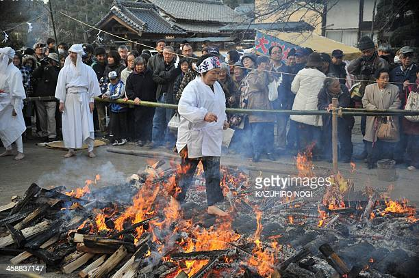 A female believer walks across embers during a fire walking ceremony to pray for good health and safety life at Kabasan Saenazumi Jinja shrine in...