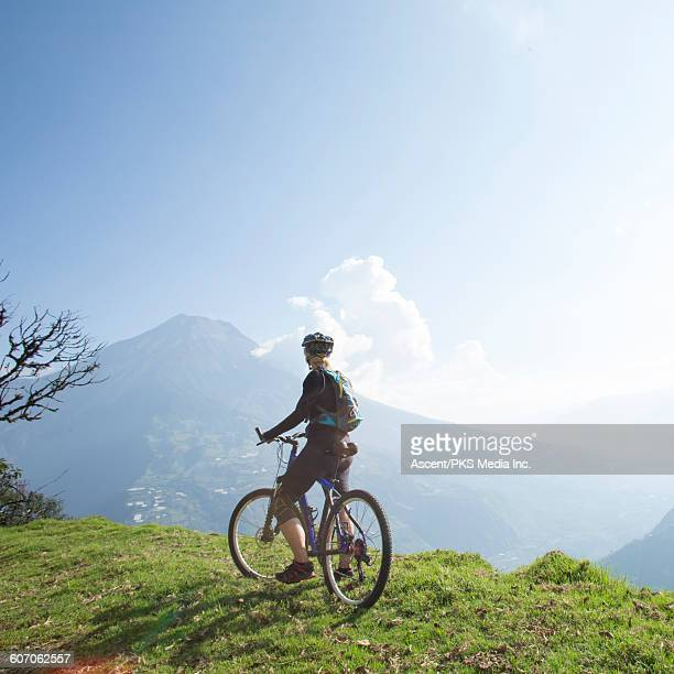 Female bicyclist pauses to admire volcano view