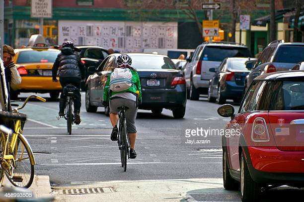 female bicyclists in new york city, greenwich village, manhattan - moving past stock photos and pictures