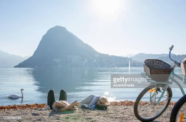 女性の自転車は地中海のビーチでリラックス - スイス ルガーノ ストックフォトと画像