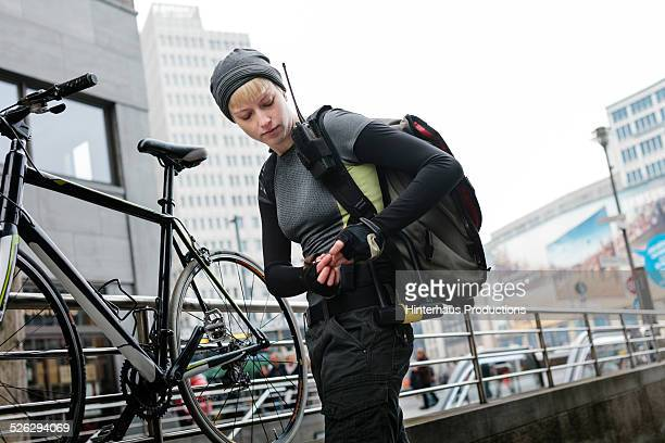 female bike messenger locking bike - bicycle messenger stock pictures, royalty-free photos & images