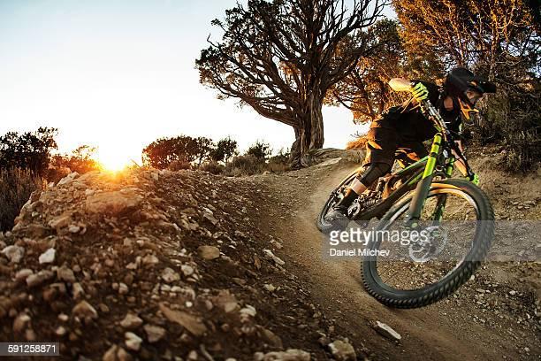 female bike racer going fast at sunset. - mountain bike bicicleta - fotografias e filmes do acervo