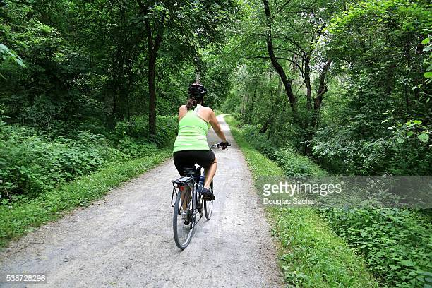 female bike rider on the towpath, cuyahoga valley national park, akron, ohio, usa - cuyahoga river stock photos and pictures