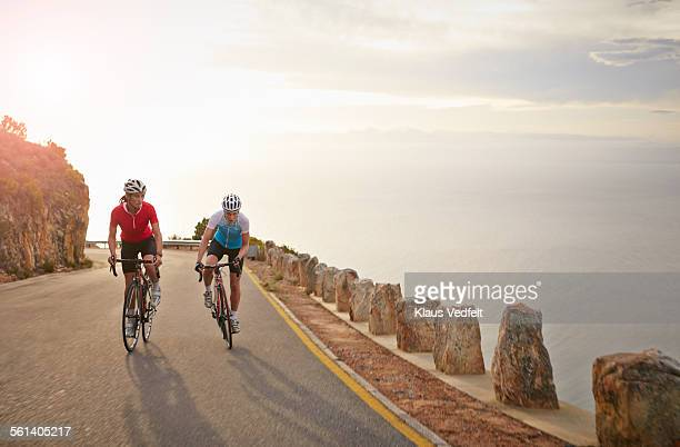 Female bike riders climbing mountain at sunset