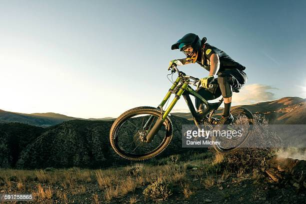 female biker jumping on her mountain bike. - mountain bike stock pictures, royalty-free photos & images