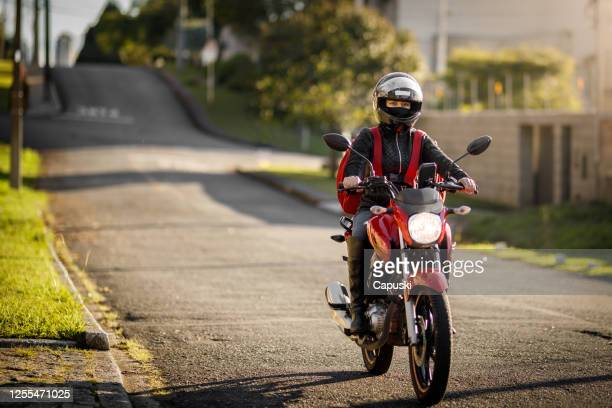 female biker riding down the street - motogirl, motoboy - helmet stock pictures, royalty-free photos & images