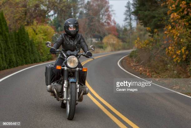 female biker riding motorcycle on country road - ecchi biker stock pictures, royalty-free photos & images