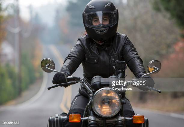 female biker wearing crash helmet while riding motorcycle on road - motorcycle biker stock pictures, royalty-free photos & images