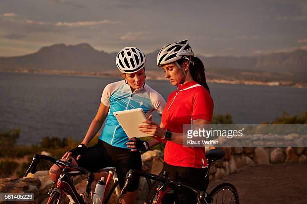 Female bikeriders having break & looking at tablet