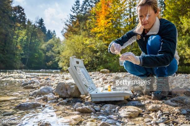 biologin fügt reagenz in eine durchstechflasche mit wasserprobe - wissenschaftlerin stock-fotos und bilder