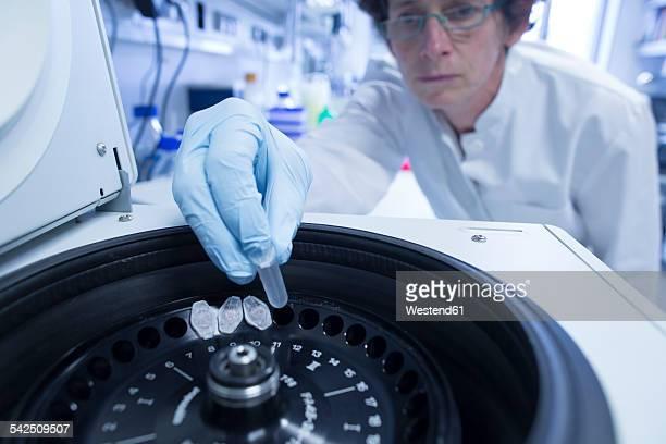 Female biologist putting tubes in centrifuge