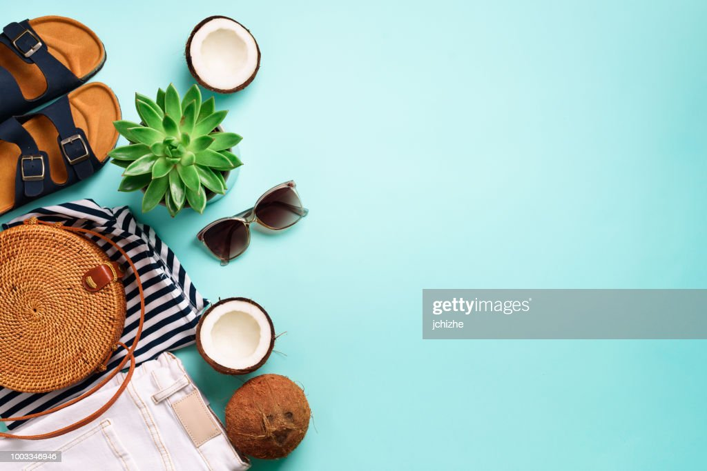 Female birkenstock sandals, jeans, striped t-shirt, rattan bag, coconut and sunglasses on blue background with copy space. Top view. Summer fashion, capsule wardrobe concept. Creative flat lay : Stock Photo