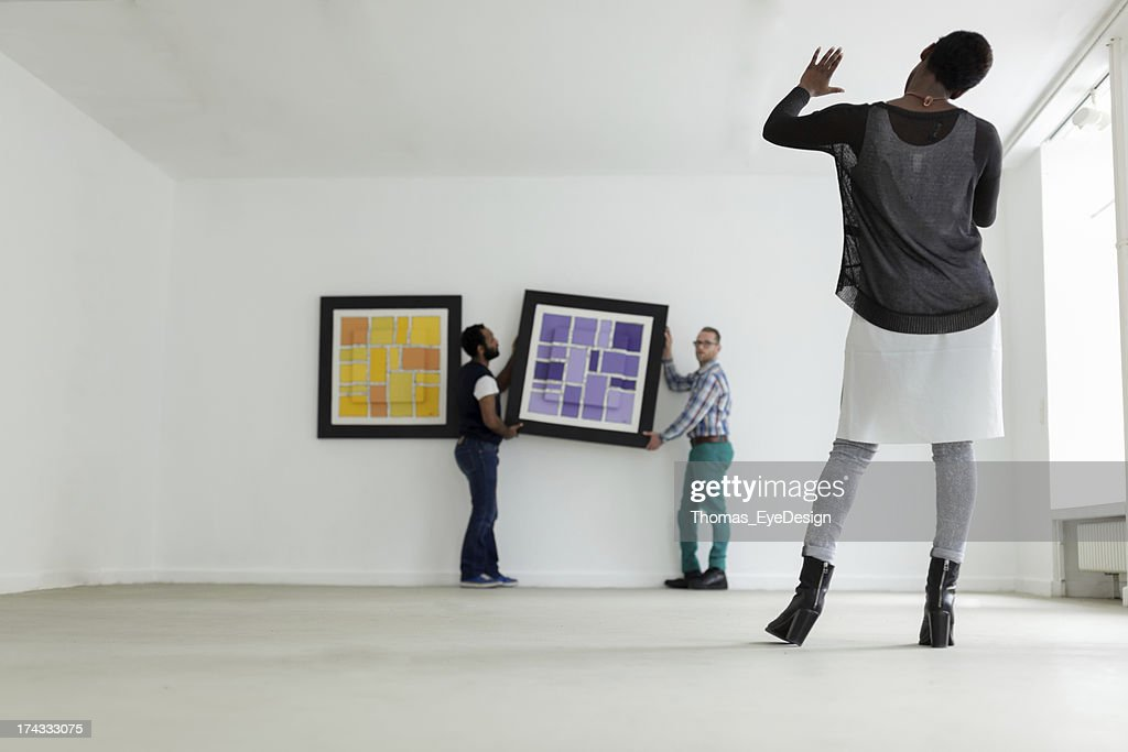 Female black Gallery owner hanging a picture : Stock Photo