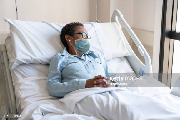 female black hospitalized patient lying in bed looking away while wearing a protective facemask - hospital stock pictures, royalty-free photos & images