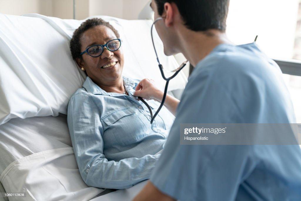 Vrouwelijke zwarte patiënt liggen op ziekenhuisbed terwijl verpleegkundige is het controleren van haar hart sloeg met de stethoscoop : Stockfoto