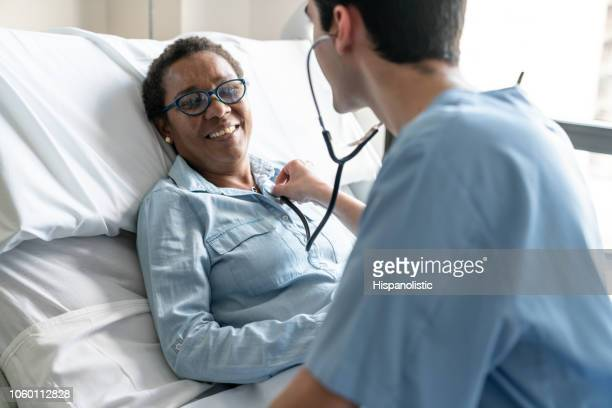 female black patient lying down on hospital bed while nurse is checking her heart beat with stethoscope - human heart stock pictures, royalty-free photos & images