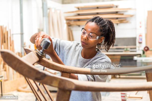 female black worker restoring an old chair in a woodworking studio - restoring stock pictures, royalty-free photos & images