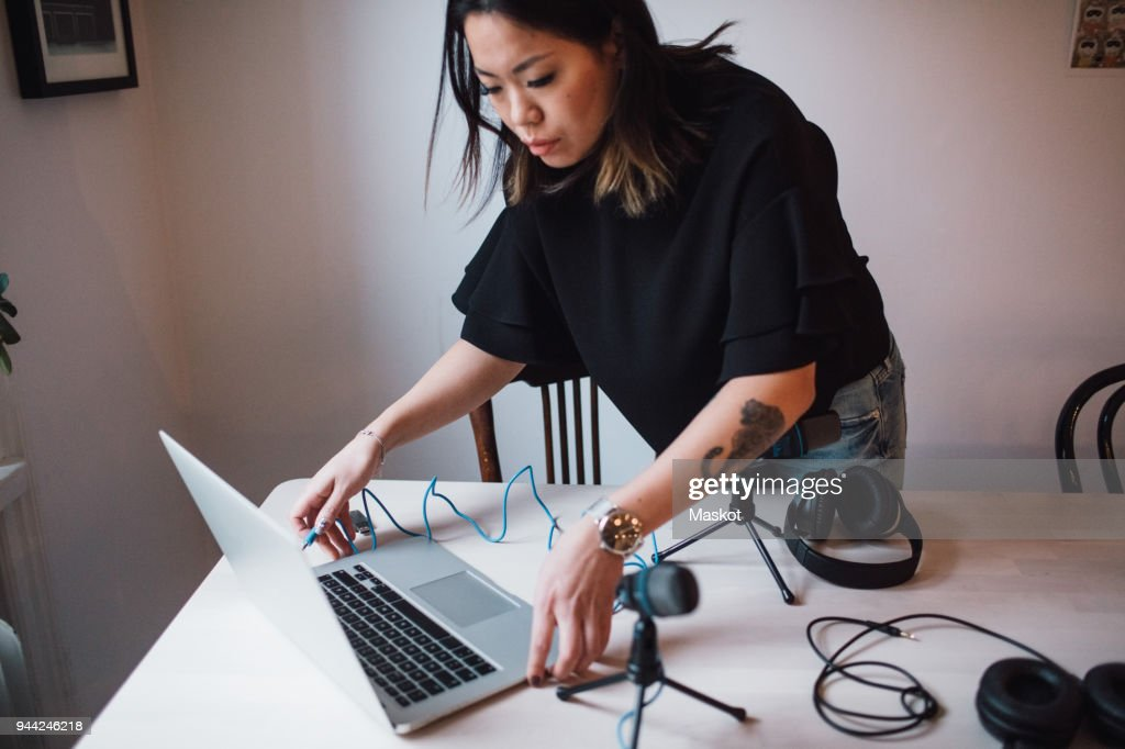 Female blogger using laptop standing by table with microphone at home : Stock Photo