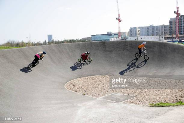 female bmx cyclists racing on incline of race track - bmx track london stock pictures, royalty-free photos & images