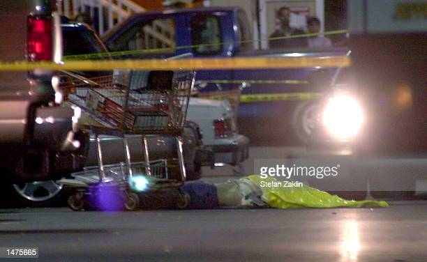 A female body is covered outside the Home Depot parking lot on October 14 2002 in Falls Church Virginia The woman was shot outside the store in what...