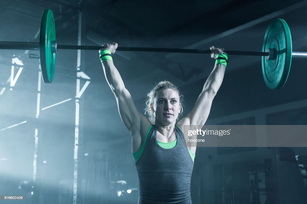 Female bodybuilder doing exercise with weights in gym : Stock Photo