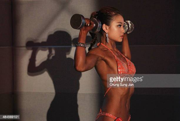 A female bodybuilder prepares for judging backstage during the 2014 NABBA/WFF Korea Championship on April 13 2014 in Daegu South Korea