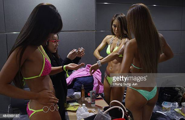 Female bodybuilders prepare themselves for judging backstage during the 2014 NABBA/WFF Korea Championship on April 13 2014 in Daegu South Korea