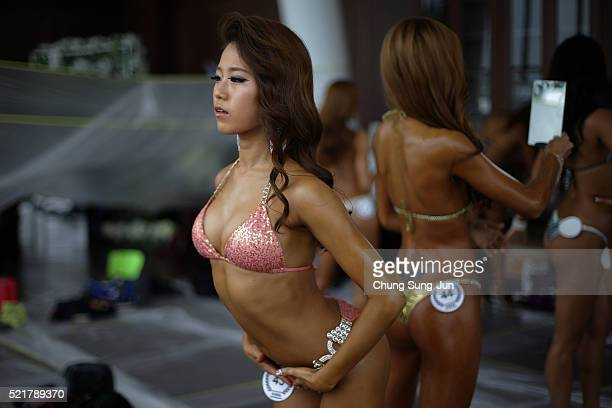 Female bodybuilders prepare themselves for judging backstage during the NABBA/WFF AsiaSeoul Open Championship on April 17 2016 in Seoul South Korea