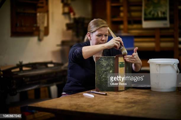 female bookbinder restoring old book - image stock-fotos und bilder