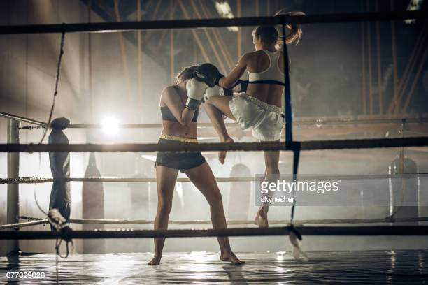 Female boxer attacking her opponent with jump knee kick.