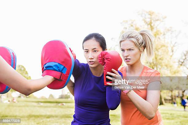 Female boxer being coached by fitness instructor