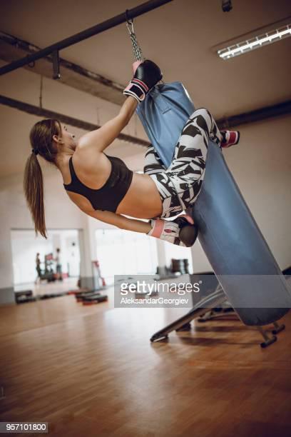 Boxer femelle faisant Abs sur le sac de boxe dans la salle de Gym