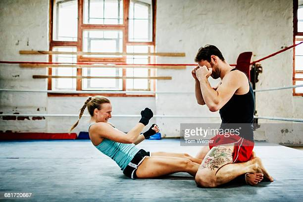 Female boxer doing situps in boxing ring