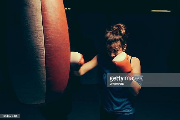 Female boxer exercising at punch bag