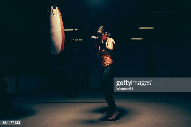 female boxer exercising at punch bag - combat sport stock pictures, royalty-free photos & images