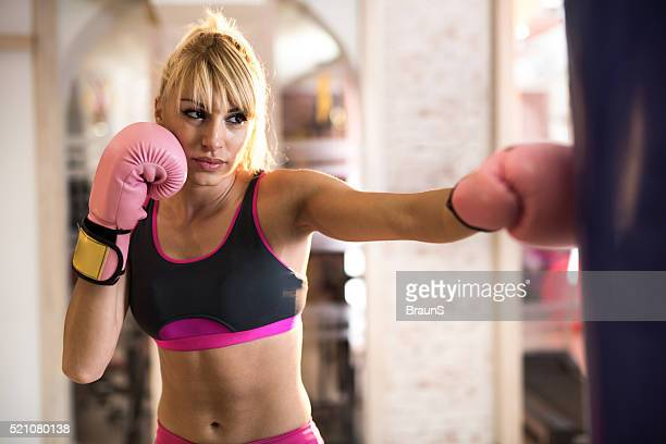 Female boxer having a sports training in a gym.