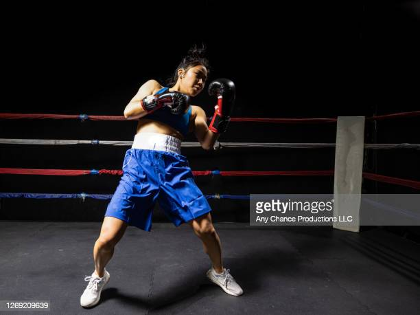 a female boxer in blue training before her sparring session. - women's boxing stock pictures, royalty-free photos & images
