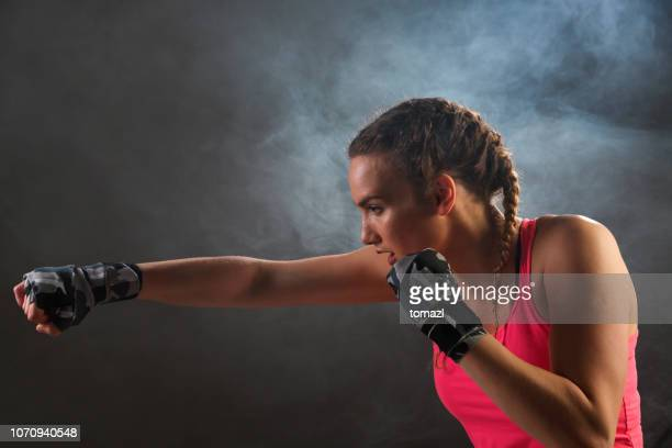vrouwelijke bokser in de mist - slaan met vuist stockfoto's en -beelden